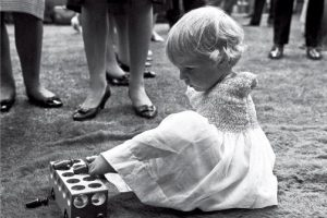 young girl with no arms due to thalidomide damage playing with a toy with her feet