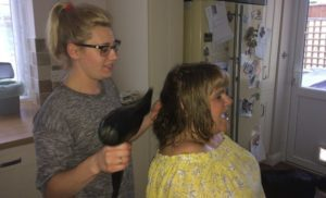Mandy's personal assistant helps her with everyday living tasks such as drying hair