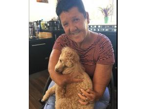 Thalidomide Trust volunteer Jean cuddling her per dog