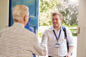 elderly man greeting a social care worker at his door