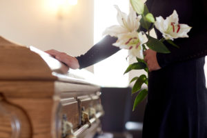 woman at a funeral putting her hand on coffin