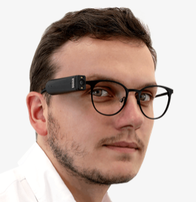 OrCam camera fitted on arm of standard glasses worn by a man