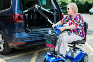 woman in wheelchair by car with hoist fitted
