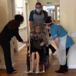 elderly lady coming out of hospital in wheelchair