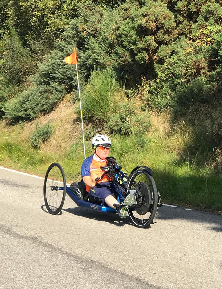 Andrew Paddison cycling on his hand bike in Scotland