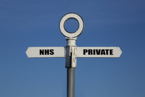 Old road sign with NHS and private pointing in opposite directions against a blue sky