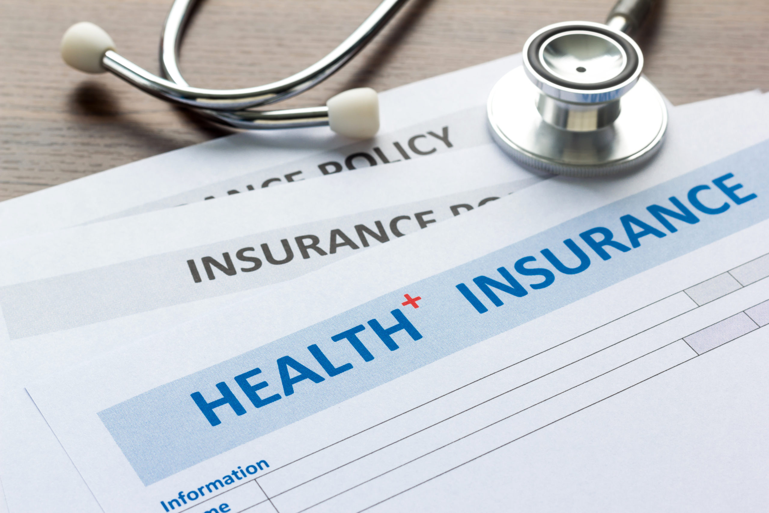 health insurance document and stethoscope